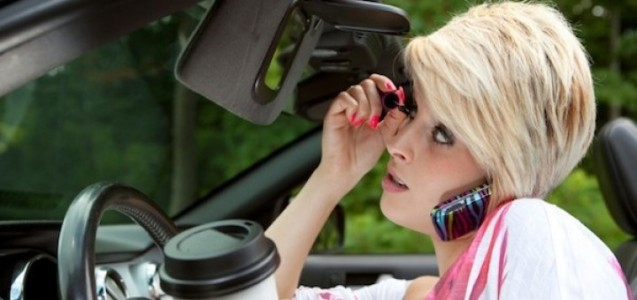 woman putting makeup on while driving